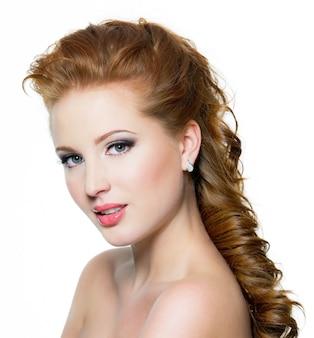 白で隔離のポーズで、美しい顔を持つ魅力的な赤毛の女性