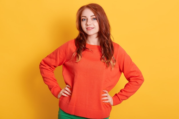 黄色の壁に立っているカジュアルなオレンジ色のプルオーバーを着て、魅力的な笑顔でカメラを直接見ている魅力的な赤い髪の女の子。前向きな感情を表現します。