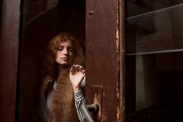 닫힌 유리 문 뒤에 서 있는 매력적인 빨간 머리 모델. 유리에 빗방울