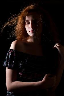 緑豊かな髪と裸の肩を持つ魅力的な赤い髪のモデル