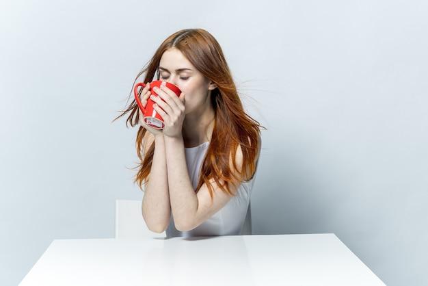 魅力的な赤毛の女性が赤いマグカップから飲んでいる間。