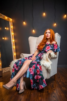 Attractive red-haired woman in a long black dress sitting on a light armchair