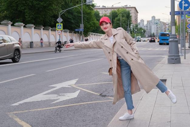 赤い野球帽とベージュのレインコートを着た魅力的な赤毛の若い女性が街道の脇に立ってタクシーに乗ります。街を歩き回る。