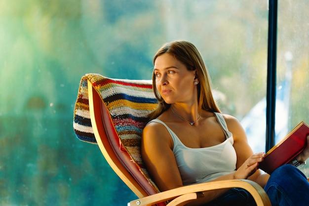 Симпатичная рыжеволосая с книжкой покачивается в удобном кресле-качалке смотрит в сторону. большие окна и уютная атмосфера.