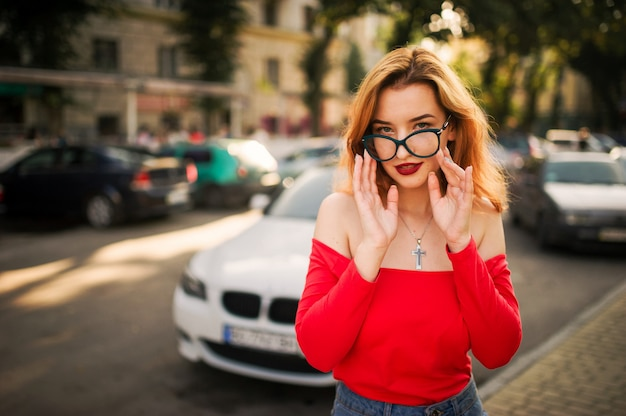 Attractive redhaired woman in eyeglasses wearing on red blouse