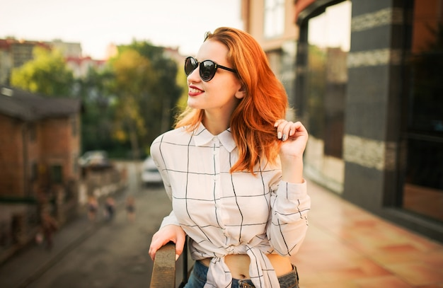 Attractive redhaired woman in eyeglasses wearing on white blouse