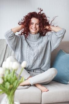Привлекательная рыжеволосая женщина в помещении с удовольствием. женщина играет со своими волосами. глупая девчонка. смешная молодая девушка.