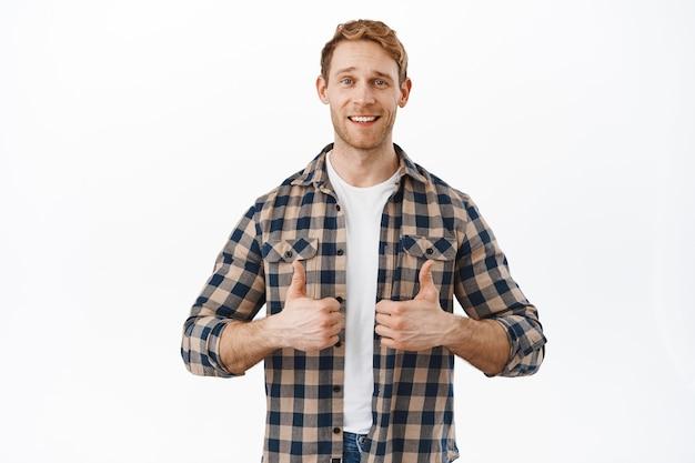魅力的な赤毛の成人男性は、親指を立てて幸せに笑い、品質に満足し、賞賛し、同意し、褒め言葉を作り、よくやった素晴らしい仕事のジェスチャーをします