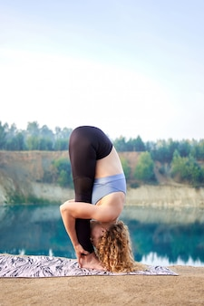 Attractive redhead curly woman or model practicing yoga outdoors