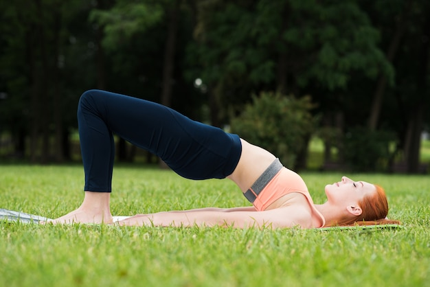Attractive redhead girl practicing yoga while lying on a mat on the grass in the park