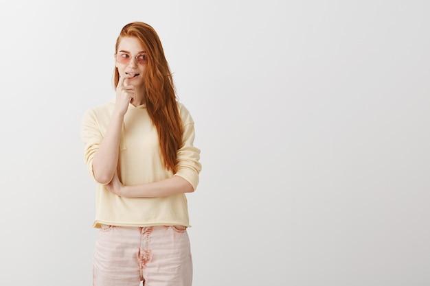Attraente ragazza rossa in occhiali da sole morde il dito e guarda a destra con la tentazione