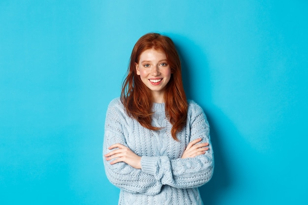 Attractive redhead girl in sweater smiling and staring at camera, standing confident against blue background.