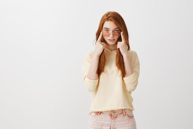 新しいサングラスをしようとしている魅力的な赤毛の女の子