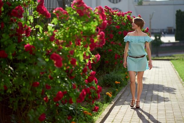 歩いてトレンディな青い光のドレスを着て魅力的な赤毛の女の子。背景に咲くバラ。