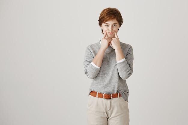흰 벽에 짧은 머리 포즈와 매력적인 빨간 머리 소녀