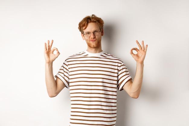 眼鏡をかけた魅力的な赤毛の男は、大丈夫な兆候を示し、感動したように見え、クールな何かを賞賛し、白い背景の上に立っています