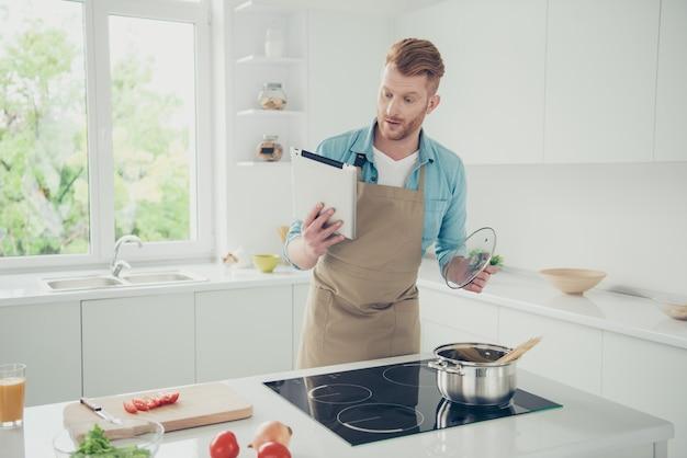 料理をしようとしているキッチンの魅力的な赤毛の男