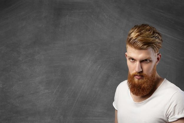 Uomo attraente hipster rossa con taglio di capelli alla moda e barba folta in posa contro la lavagna vuota con copia spazio per il testo o contenuto promozionale, guardando con rabbia.