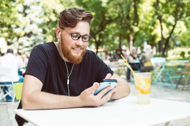Attractive redhead man with a beard listens to music on a mobile phone while sitting at a cafe table.
