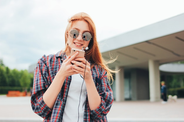 Attractive redhead smiling girl in round sunglasses with phone in her hands