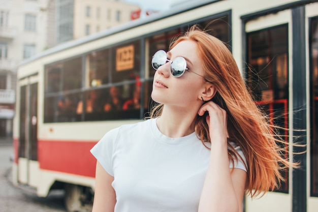 Attractive redhead smiling girl in sunglasses in casual clothes on tram background at street