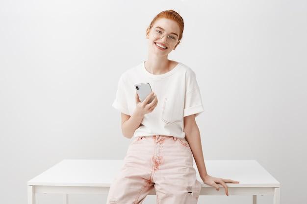 携帯電話を使用してフレンドリーなメガネの魅力的な赤毛の女性