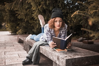 Attractive redheadwoman in hat lying on bench with book