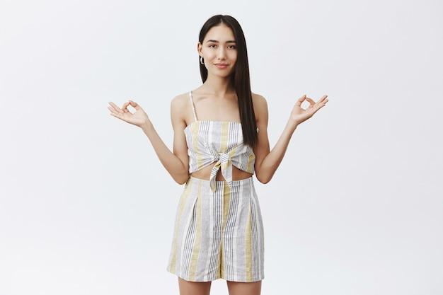 Attraente femmina asiatica rilassata con lunghi capelli scuri naturali che diffondono le mani in un gesto zen, sorridendo e guardando con sguardo pacifico durante la meditazione o lo yoga