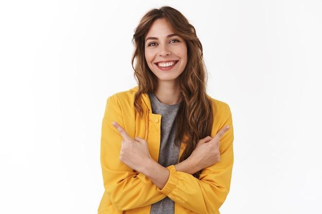 옆으로 손을 교차하는 매력적인 편안하고 웃는 행복한 유럽 여성이 왼쪽 오른쪽 제품 복사 공간을 보여주며 프로모션, 흰색 벽 사이에서 웃으면서 따기