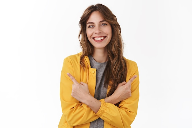 Attractive relaxed smiling happy european woman pointing sideways hands crossed body show left right product copy space grinning picking between promos, white wall
