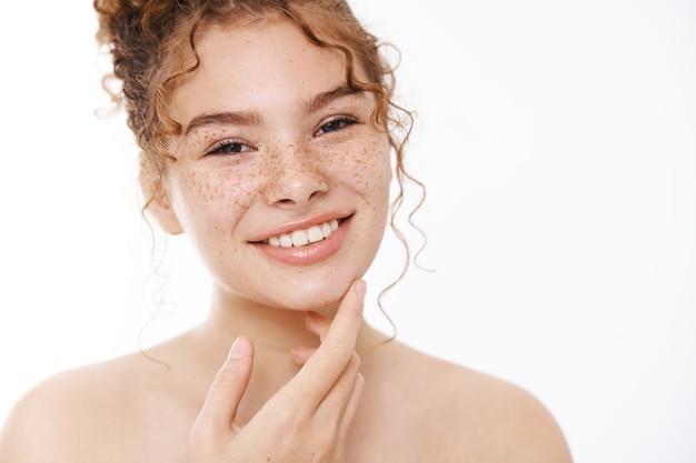 매력적인 안도의 행복한 부드러운 빨간 머리 소녀 얼굴 주근깨가 만족스럽게 웃고 있으며 피부과 전문의 처방전을 통해 완벽한 피부 상태를 즐기며 만족스럽게 턱 손가락을 만지고 있습니다.