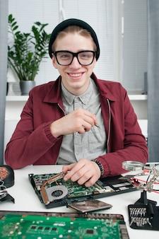 カメラに微笑んでメガネの魅力的な修理工。