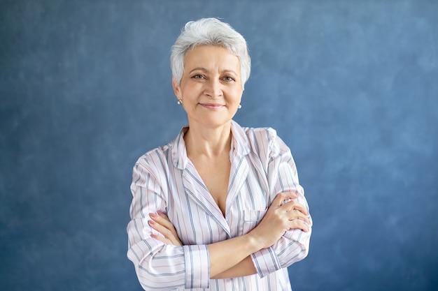 彼女の胸に腕を組んで自信を持って笑顔でポーズをとる短い白髪の魅力的な引退した女性