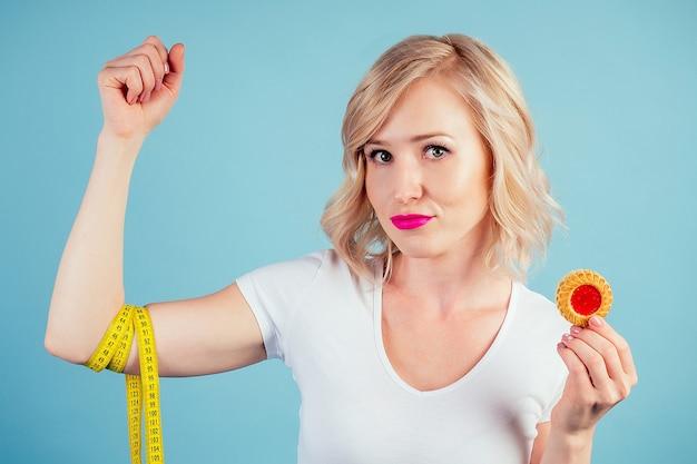 Привлекательная грустная блондинка с макияжем и губами цвета фуксии держит высококалорийное печенье с измерительной лентой в студии на синем фоне. диета и отказ от мучных изделий