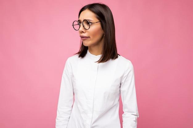 毎日のスタイリッシュな服と横を向いているカラフルな表面の壁に分離されたモダンな光学メガネを身に着けている魅力的な悲しい動揺悲しげな若い黒髪の女性