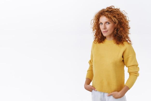 黄色いセーターを着た魅力的な生意気な赤毛の巻き毛の女性起業家、白い壁を半分ひっくり返して立っている、ジーンズのポケットに手を入れて、笑顔で正面を見て自信を持って、断定的な視線