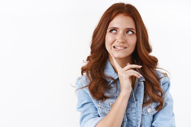 Attraente donna rossa impertinente in giacca di jeans, sembra curiosa, morde il labbro inferiore dalla tentazione, tocca il mento guarda da parte come meditando, pensando a quale ordine, stando pensierosa