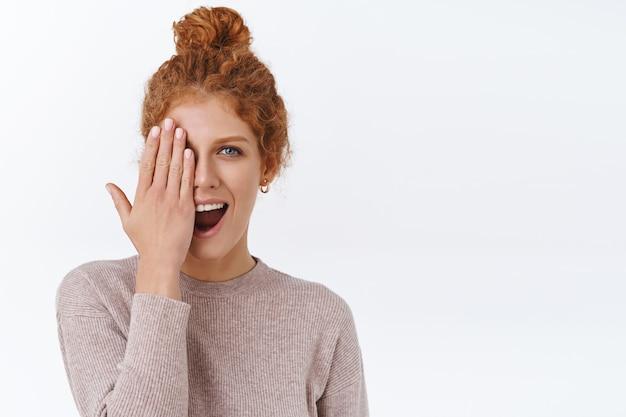 곱슬머리를 한 매력적인 빨간 머리 여성, 얼굴 한쪽을 가리고, 손을 보여주고, 새로운 매니큐어를 보여주고, 놀란 미소를 짓고, 흰 벽
