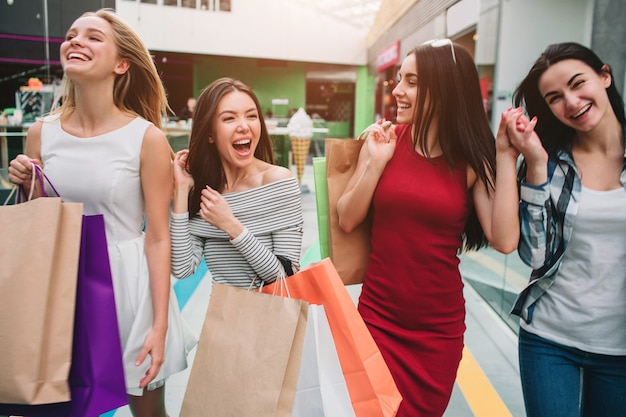 Attractive and satisfied girls are walking in mall together. they are holding bags with stuff. girls are laughing and having some fun.