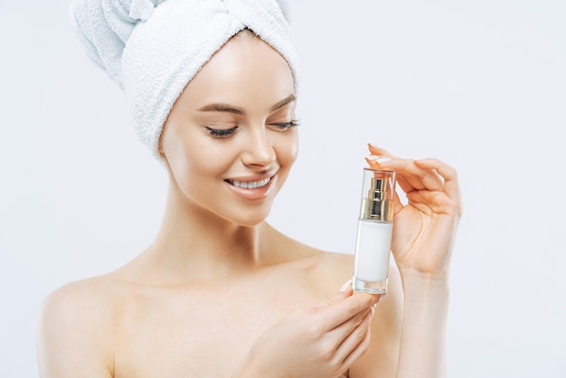 Attractive satisfied woman applies moisturizer, holds bottle of skin cream or lotion
