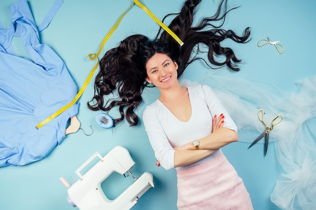 Attractive seamstress tailor (dressmaker) designer of wedding dresses lying on the floor with sewing machine, coats on a hanger and measuring tape on a blue background in the studio view from above.