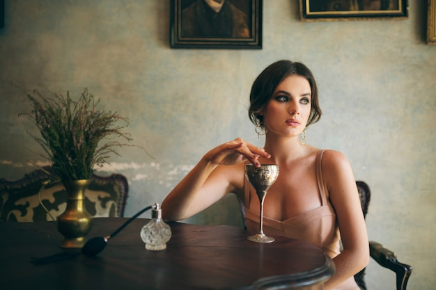 Привлекательная соблазнительная чувственная стильная женщина в платье бохо сидит в винтажном ретро-кафе и пьет вино из стекла