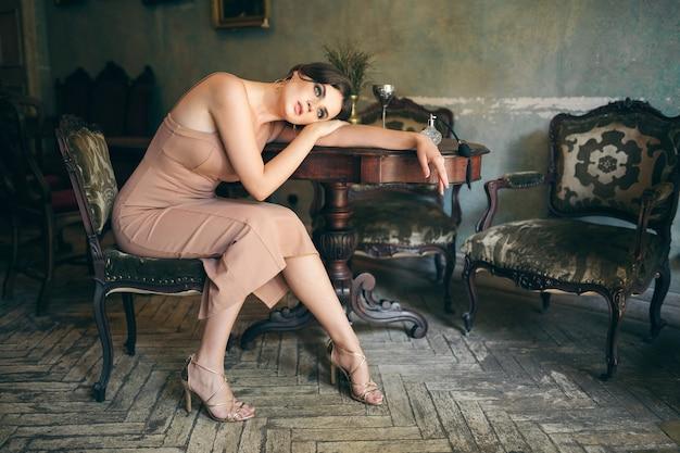 Привлекательная соблазнительная чувственная стильная женщина в платье бохо, сидящая в винтажном ретро-кафе с духами
