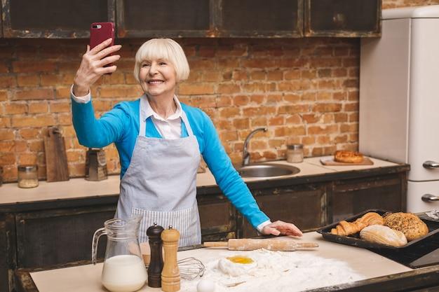 魅力的な年配の女性はキッチンで調理しています。祖母がおいしい焼き菓子を作る。自分撮り写真に電話を使用しています。