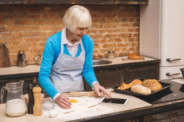 Привлекательная женщина старшего возраста готовит на кухне. бабушка делает вкусную выпечку. с помощью планшетного компьютера.