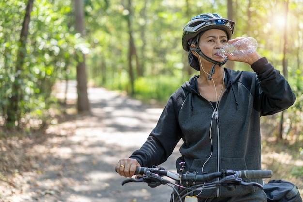 魅力的な上級アジアの女性は公園で自転車のボトルから水を飲む