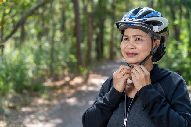 Attractive senior asian woman with bicycle in park