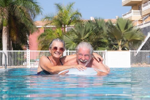풍선 매트리스를 가지고 노는 수영장에 떠 있는 매력적인 수석 부부. 여름 휴가와 태양을 즐기는 행복한 은퇴한 사람들