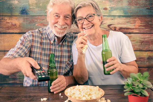 매력적인 수석 몇 tv에서 축구 경기를보고, 맥주를 마시고, 팝콘을 먹는 재미. 나무 배경