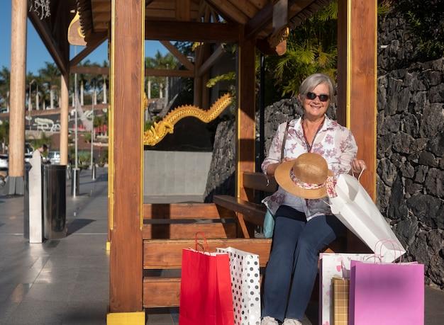 ショッピングモールの外に座っている魅力的な年配の女性-彼女の購入に満足しています。